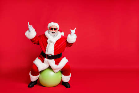 Full length body size view of his he nice attractive cheerful cheery glad fat bearded Santa working out sitting on pilates ball showing horn sign heavy metal isolated over bright vivid shine red background Archivio Fotografico - 129822359