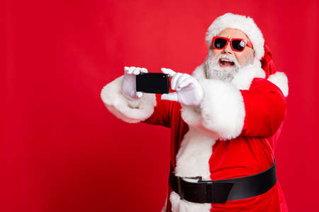Portrait of excited santa claus in eyewear making selfie with cell phone device on christmas vacation smiling wearing belt isolated over red background