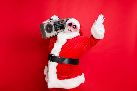 Forever young. Portrait of crazy style santa claus in eyewear eyeglasses raising palms holding retro cassette dancing having christmas party isolated over red background