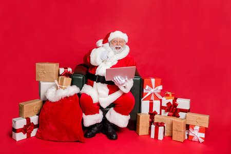 Nice cheerful excited glad hard-working fat bearded man delivering purchases shop delivery checking address list clients children orders isolated on bright vivid shine red background
