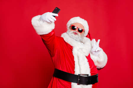 Portrait of his he nice attractive cheerful cheery positive flirty bearded Santa pouted lips taking making selfie having fun showing v-sign isolated over bright vivid shine red background