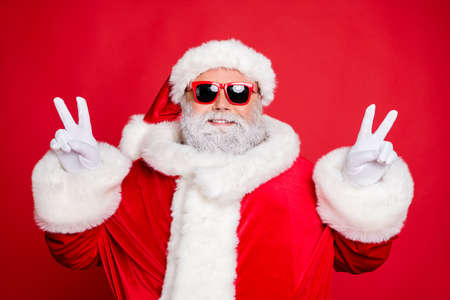 Close-up portrait of his he nice attractive cheerful cheery peaceful bearded Santa showing double v-sgn festive festal mood isolated over bright vivid shine red background Reklamní fotografie