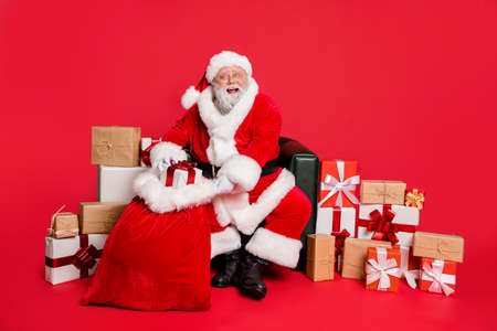 Portrait of nice cheerful cheery generous fat bearded man St Nicholas packing preparing fairy miracle orders winter december holly jolly isolated over bright vivid shine red background Reklamní fotografie
