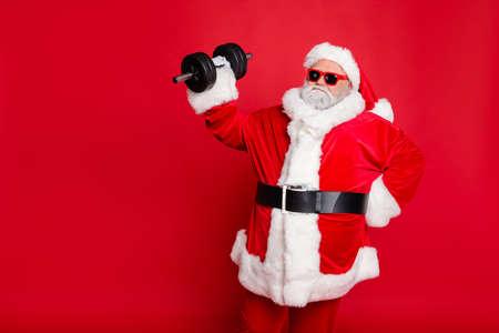 Ritratto del suo bel attraente grasso sovrappeso barbuto Babbo Natale che risolve bilanciere esercizio fisico allenamento calorie dieta isolato su sfondo rosso brillante vivido lustro
