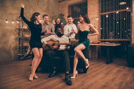 Full body photo of charming fellows enjoy song played by mulatto celebrate christmas night on x-mas party in house with newyear illumination indoors