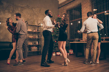 Full body photo of cheerful multinational fellows dance enjoy disco christmas party x-mas holidays in house with newyear lights indoors