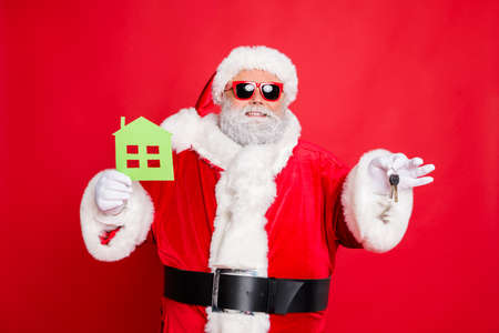 Portrait of cheerful santa claus in eyewear eyeglasses holding keys and paper card building give move house present wearing hat cap belt isolated over reed background