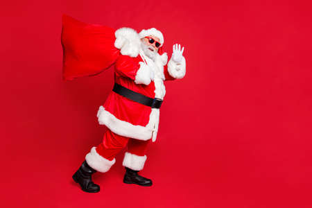 Full length body size view of cheerful cheery funky fat overweight plump gray-haired bearded man piggy backing gifts winter tradition waving greetings isolated over bright vivid shine red background