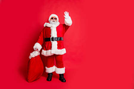 Full length body size view of his he cheerful funky fat overweight plump gray-haired bearded man carrying purchases waving greetings congrats tradition isolated over bright vivid shine red background Stock Photo
