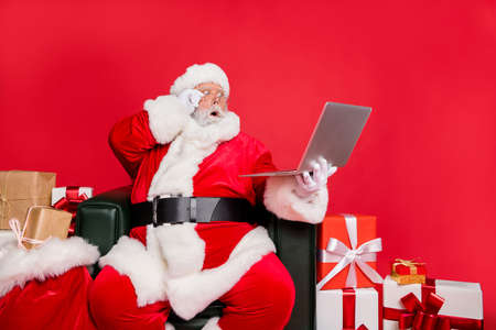 Stunned hard-working fat bearded man St Nicholas sitting on armchair shop delivery checking address list clients web orders fairy dream christmastime isolated on bright vivid shine red background