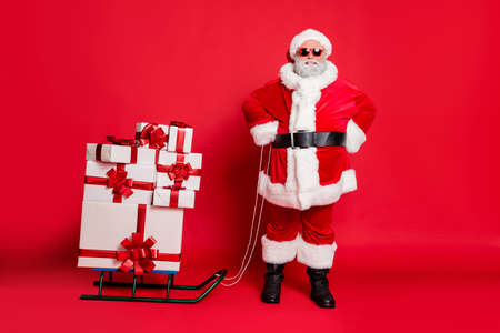 Full length photo of cheerful santa claus in eyewear eyeglasses having sledge carry presents for christmas night isolated over red background