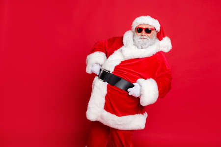 Portrait of his he nice attractive cheerful cheery content bearded Santa showing eve noel festive festal mood holding belt isolated over bright vivid shine red background