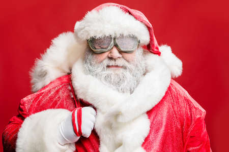 Close up photo of stylish elderly hipster santa carry bag sack ready deliver present in stormy cataclysm wear white gloves fur sleeves cap isolated over red color background Stock fotó - 129822961