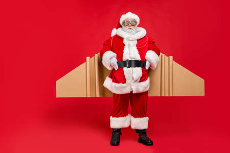 Full size photo of funky super pensioner in santa claus costume ready to hurry on speed cardboard imagine travel craft wings wear cap goggles hat isolated over red background 版權商用圖片