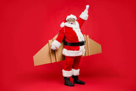 Full length photo of funny shocked elderly superhero pensioner in santa claus hat costume ready to travel craft flight fly up travel wear xmas cap pants isolated over red color background
