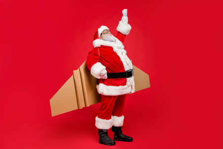 Ready set go. Full length photo of of grey-hair funky hipster super santa in goggles start his countdown fairy flight up fly wear cap hat pants belt isolated over red color background 版權商用圖片