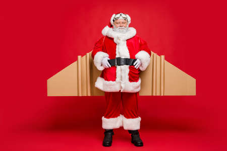 Ready for flight. Full length photo of cool charming santa claus with airplane cardboard imagine wings wear fairy costume belt isolated over red color background
