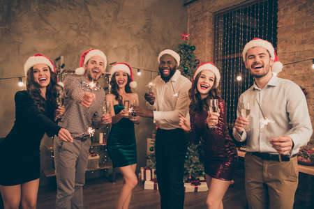 Portrait of funny fellows with santa claus hat cap hold champagne bengal lights celebrate christmas holidays x-mas night party in house indoors Stock Photo
