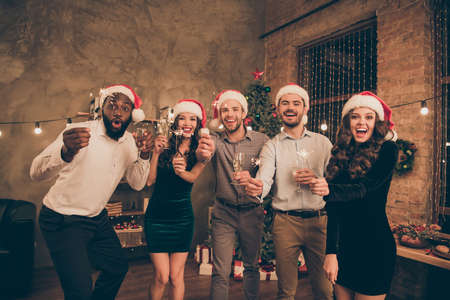 Portrait of lovely guys ladies hold fireworks glass enjoy christmas time celebrate x-mas midnight wearing santa claus hat cap formal wear in house with noel illumination indoors Stock Photo