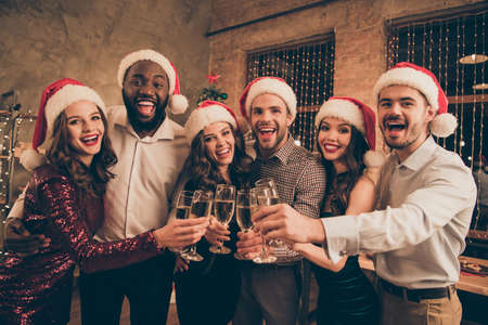Portrait of cheerful buddies cheering chilling celebrate christmas time enjoy x-mas midnight give toast in house with noel decoration indoors