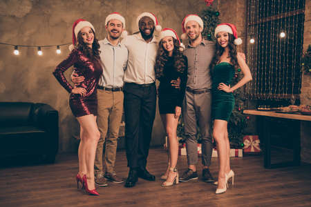 Full length photo of charming ladies and guys in santa claus have fun enjoy christmas time celebrate x-mas party in house with noel decoration indoors Imagens