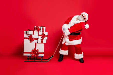 Fulll length photo of tired santa claus pulling his sledge with packages gifts on midnight wearing eyeglasses eyewear belt isolated over red background