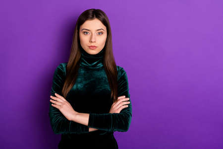 Portrait of focused person with crossed hands looking at camera isolated over purple violet background