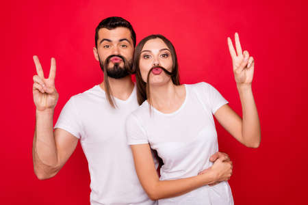 Portrait of his he her she nice attractive charming cool cheerful cheery playful foolish spouses buddy fellow having fun showing v-sign fooling isolated over bright vivid shine red background Фото со стока