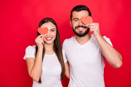 Photo of fashionable stylish casual trendy funky couple of two lovely cheerful people together hiding their eyes behind small heart shaped cards while wearing white t-shirt isolated with red background Фото со стока