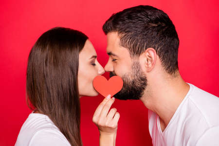 Photo of charming cute pretty sweet cheerful positive couple two people of spouses together wearing t-shirts kissing each other behind small red heart isolated with background