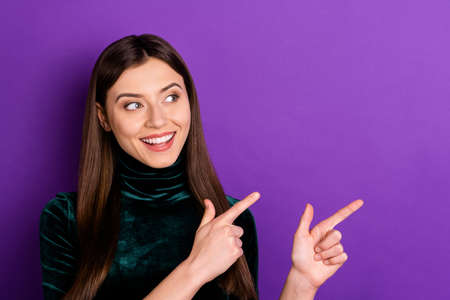 Portrait of pretty person looking pointing at copy space wearing turtleneck isolated over purple violet background