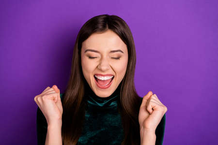 Close up photo of charming funny lady raising her fists shouting yeah wearing black turtleneck isolated over purple violet background