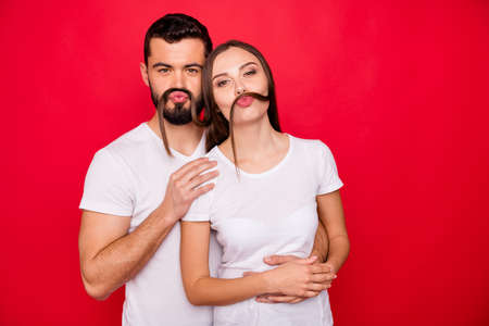 Portrait of his he her she nice attractive lovely cheerful cheery playful foolish married spouse buddy fellow spending free time having fun grimacing isolated over bright vivid shine red background Фото со стока - 129823115