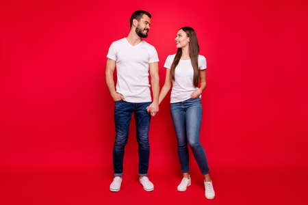 Full length body size view of his he her she nice attractive lovely affectionate tender sweet cheerful cheery married spouses life partners holding hands isolated on bright vivid shine red background
