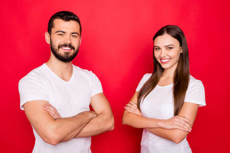Photo of two date cheerful kind glad happy people together standing confidently wearing white t-shirts while isolated over red background Stock Photo