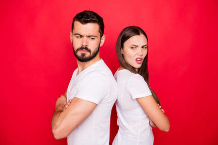 Photo of sad upset unhappy trendy stylish white people wearing t-shirts offensively looking at each other while isolated with red background