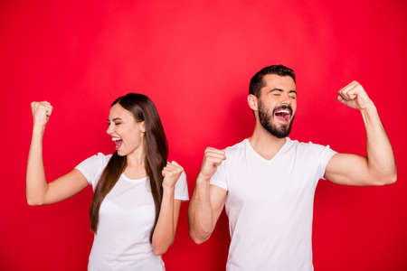 Photo of two trendy rejoicing overjoyed people celebrating their victorious day congratulating each other while isolated with red background