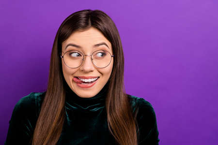 Close up photo of pretty teenager looking licking lips having eyeglasses eyewear isolated over purple violet background Фото со стока