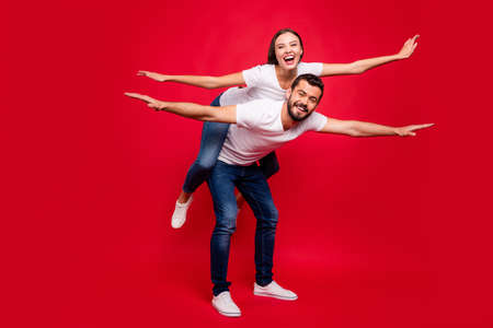 Full length body size photo of two charming stylish cute nice trendy casual people together wearing jeans denim white t-shirts pretending to be airplanes isolated with red background