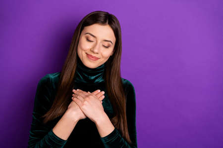 Portrait of charming person with her eye closed putting palms on chest isolated over purple violet background Stock fotó