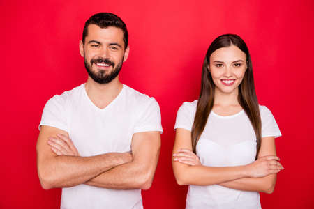 Photo of two charming casual beautiful cute handsome pretty sweet trendy nice people together coworking while wearing white t-shirts isolated over red background