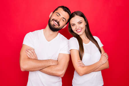 Photo of two white pretty lovely sweet handsome beautiful people with man bearded brunette wearing white t-shirt standing confidently while isolated with red background