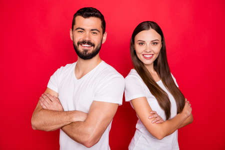 Photo of cute pretty trendy couple of two people standing back to back to each other while isolated with red background wearing trendy white t-shirt