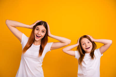 Portrait of cute impressed people with long haircut screaming wow omg wearing white t-shirt isolated over yellow background Stock Photo
