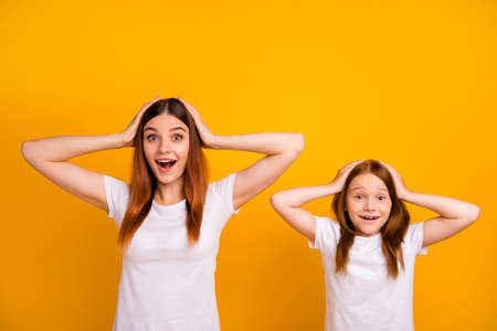 Portrait of impressed mom with her daughter having long haircut touching their head screaming wow omg isolated over yellow background