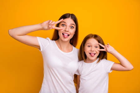 Portrait of two nice attractive lovely comic crazy childish cheerful cheery glad positive person showing v-sign having fun fooling isolated over bright vivid shine yellow background