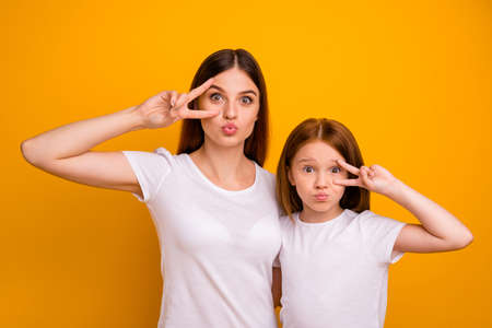 Portrait of two nice attractive comic childish funky cheerful glad positive person mommy showing v-sign having fun holiday isolated over bright vivid shine yellow background