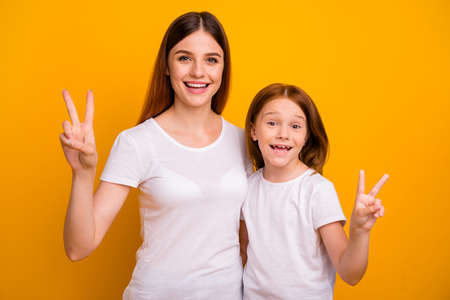 Portrait of two nice attractive lovely funky funny cheerful cheery optimistic glad positive person showing v-sign having fun isolated over bright vivid shine yellow background