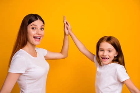 Portrait of cheerful mom and her daughter with long hairdo clapping palm laughing wearing white t-shirt isolated over yellow background