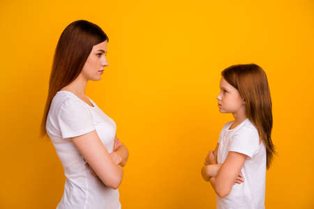 Profile side photo of negative mom and her child with long haircut looking wearing white t-shirt isolated over yellow background Stock Photo